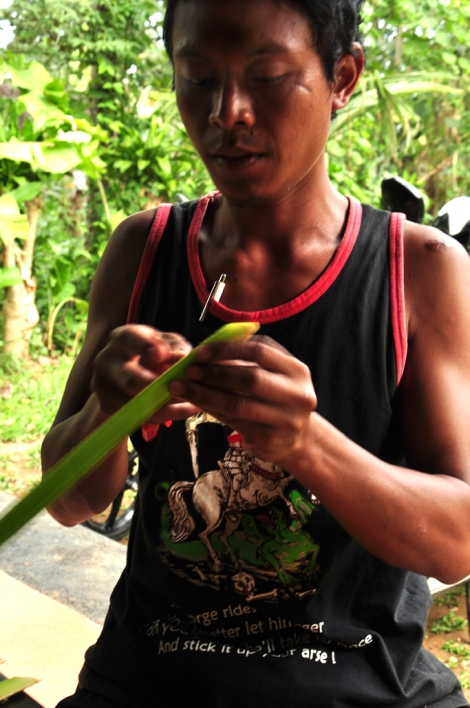 Minggu demonstrating how to make a ceremonial flower from coconut palm leaf